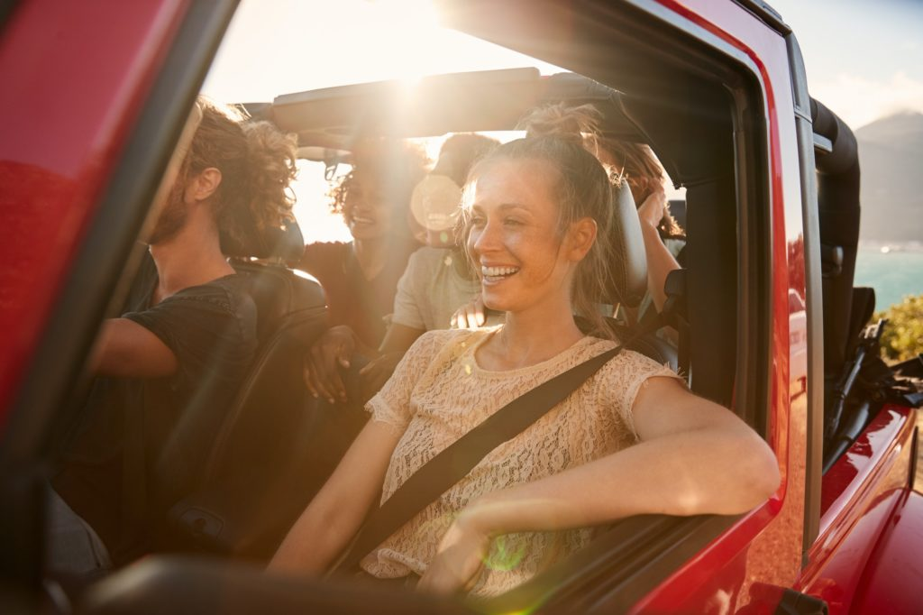 Happy millennial friends on a road trip vacation driving in an open car, close up, lens flare